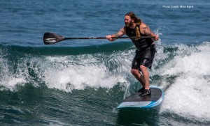 Male Stand-up Paddle (SUP) surfer with tattoos, long hair, and b